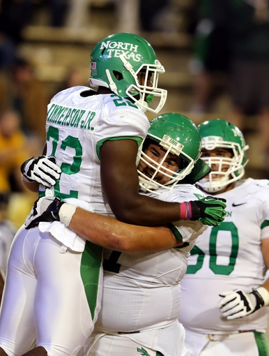 Oct 26, 2013; Hattiesburg, MS, USA; North Texas Mean Green running back Antoinne Jimmerson (22) celebrates a touchdown run with teammate Mason Y'Barbo (57) in the second quarter of their game against the Southern Miss Golden Eagles at M.M. Roberts Stadium. Mandatory Credit: Chuck Cook-USA TODAY Sports