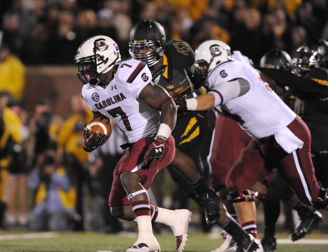 Oct 26, 2013; Columbia, MO, USA; South Carolina Gamecocks running back Shon Carson (7) runs the ball as Missouri Tigers defensive lineman Kony Ealy (47) defends during the first half at Faurot Field. Mandatory Credit: Denny Medley-USA TODAY Sports