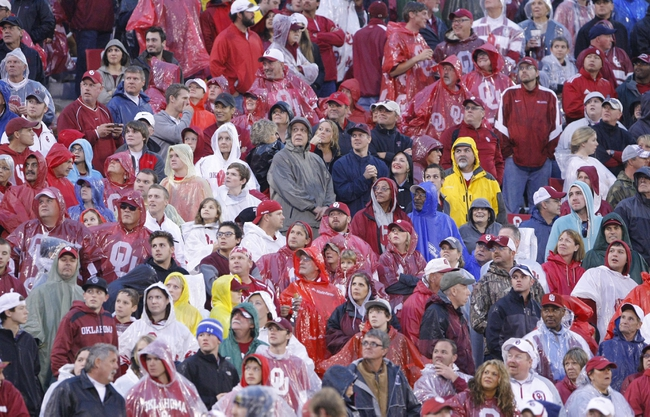 Oct 26, 2013; Norman, OK, USA; The fans watch a replay in the rain during the third quarter of a game between Texas Tech Red Raiders and the Oklahoma Sooners at Gaylord Family - Oklahoma Memorial Stadium. Oklahoma won 38-30.  Mandatory Credit: Alonzo Adams-USA TODAY Sports