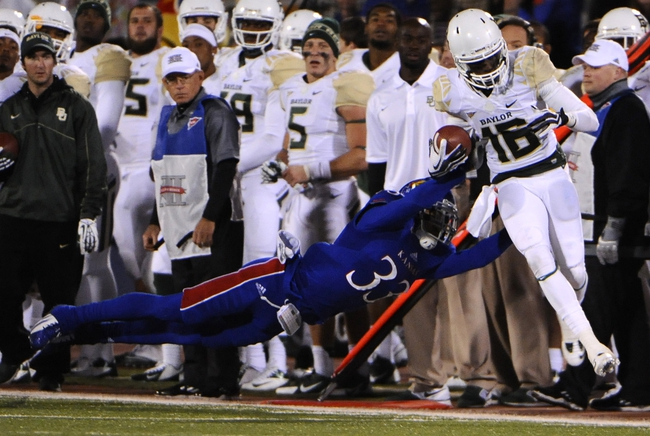 Oct 26, 2013; Lawrence, KS, USA; Baylor Bears wide receiver Tevin Reese (16) runs with the ball as Kansas Jayhawks linebacker Cassius Sendish (33) tackles in the second half at Memorial Stadium. Mandatory Credit: John Rieger-USA TODAY Sports