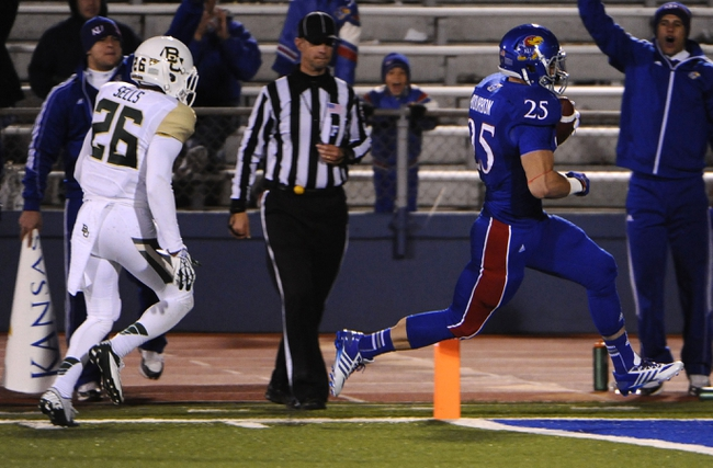 Oct 26, 2013; Lawrence, KS, USA; Kansas Jayhawks running back Brandon Bourbon (25) scores a touchdown against Baylor Bears safety Taion Sells (26) in the second half at Memorial Stadium. Baylor won 59-14. Mandatory Credit: John Rieger-USA TODAY Sports