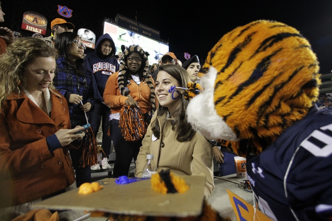 Oct 26, 2013; Auburn, AL, USA; Auburn Tigers mascot Aubie paints a tiger paw on the face of Caroline McGill during the second half of the game against the Florida Atlantic Owls at Jordan Hare Stadium. Mandatory Credit: John Reed-USA TODAY Sports
