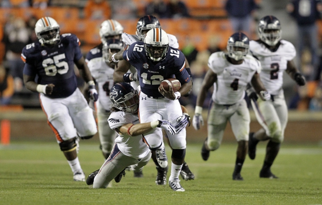 Oct 26, 2013; Auburn, AL, USA; Auburn Tigers quarterback Jonathan Wallace (12) is tackled by Florida Atlantic Owls safety Mark Mauro (8) during the second half at Jordan Hare Stadium. Mandatory Credit: John Reed-USA TODAY Sports