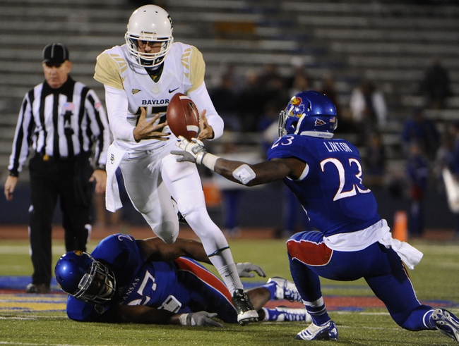 Oct 26, 2013; Lawrence, KS, USA; Baylor Bears quarterback Seth Russell (17) fumbles the ball against Kansas Jayhawks linebacker Victor Simmons (27) and safety Dexter Linton (23) in the second half at Memorial Stadium. Baylor won 59-14. Mandatory Credit: John Rieger-USA TODAY Sports