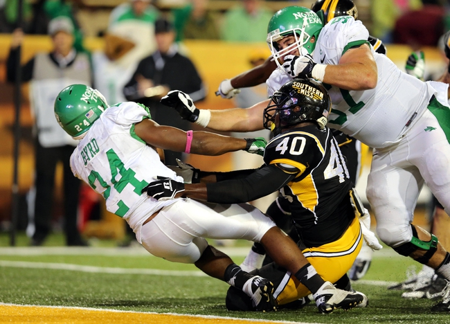 Oct 26, 2013; Hattiesburg, MS, USA; North Texas Mean Green running back Brandin Byrd (24) scores a fourth quarter touchdown as Southern Miss Golden Eagles linebacker C.J. Perry (40) defends at M.M. Roberts Stadium. North Texas won, 55-14. Mandatory Credit: Chuck Cook-USA TODAY Sports