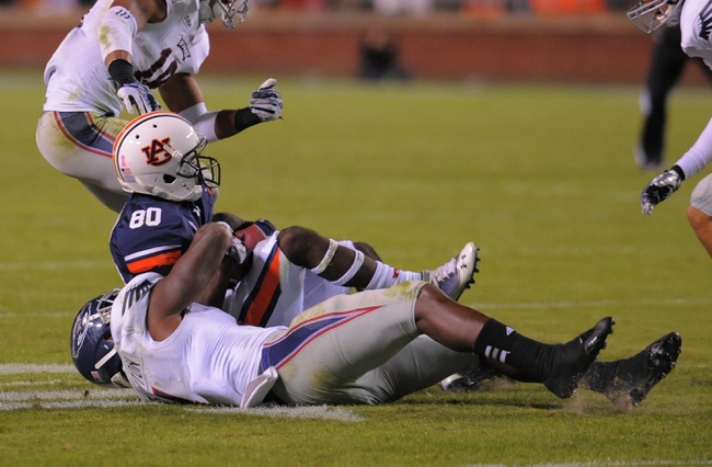 Oct 26, 2013; Auburn, AL, USA; Florida Atlantic Owls linebacker Adarius Glanton (4) brings down Auburn Tigers wide receiver Marcus Davis (80) in the second half at Jordan Hare Stadium. The Tigers beat the Owls 45-10. Mandatory Credit: Shanna Lockwood-USA TODAY Sports