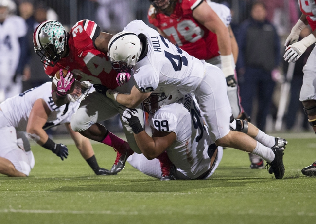 Oct 26, 2013; Columbus, OH, USA; Ohio State Buckeyes running back Carlos Hyde (34) fights through a tackle attempted by Penn State Nittany Lions defensive tackle Austin Johnson (99) and  Mike Hull (43) at Ohio Stadium. Mandatory Credit: Greg Bartram-USA TODAY Sports