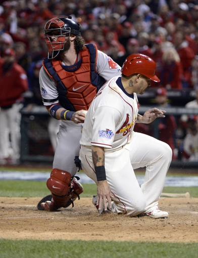 Oct 26, 2013; St. Louis, MO, USA; St. Louis Cardinals catcher Yadier Molina (right) is tagged out by Boston Red Sox catcher Jarrod Saltalamacchia (left) in the 9th inning during game three of the MLB baseball World Series at Busch Stadium. Mandatory Credit: Eileen Blass-USA TODAY Sports