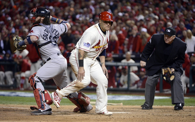 Oct 26, 2013; St. Louis, MO, USA; Boston Red Sox catcher Jarrod Saltalamacchia (39) throws to third base after tagging out St. Louis Cardinals catcher Yadier Molina (middle) as umpire Dana Demuth (right) looks on in the 9th inning during game three of the MLB baseball World Series at Busch Stadium. Mandatory Credit: Eileen Blass-USA TODAY Sports