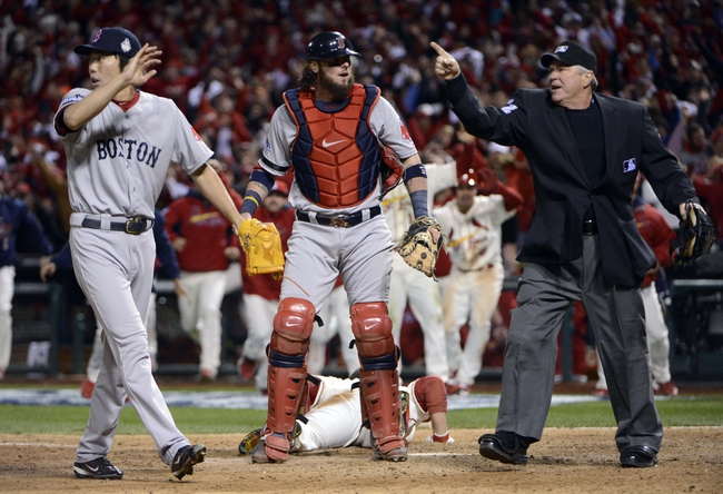 Oct 26, 2013; St. Louis, MO, USA; Boston Red Sox relief pitcher Koji Uehara (left) and catcher Jarrod Saltalamacchia (middle) react after home plate umpire Dana Demuth makes an obstruction call allowing the St. Louis Cardinals winning run to score during game three of the MLB baseball World Series at Busch Stadium. Mandatory Credit: Eileen Blass-USA TODAY Sports
