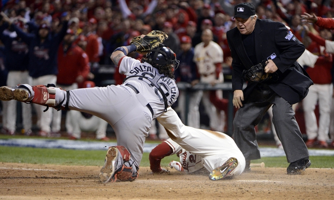 Oct 26, 2013; St. Louis, MO, USA; Boston Red Sox catcher Jarrod Saltalamacchia (39) shows the ball to umpire Dana Demuth (right) after applying a tag on St. Louis Cardinals pinch hitter Allen Craig (middle) in the 9th inning during game three of the MLB baseball World Series at Busch Stadium. Craig was called safe on an obstruction call. Mandatory Credit: Eileen Blass-USA TODAY Sports