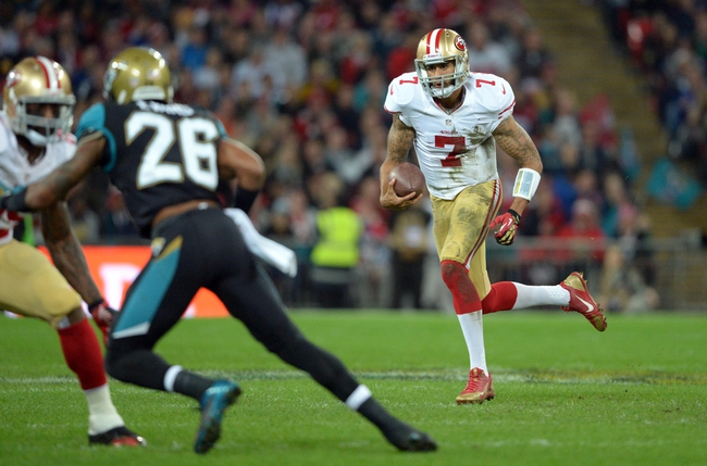 Oct 27, 2013; London, UNITED KINGDOM; San Francisco 49ers quarterback Colin Kaepernick (7) runs against Jacksonville Jaguars free safety Josh Evans (26) in the first half during an International Series game at Wembley Stadium. Mandatory Credit: Bob Martin-USA TODAY Sports