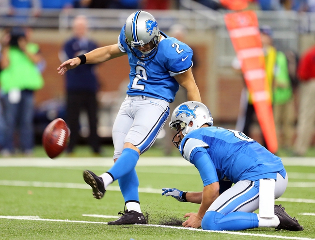 Oct 27, 2013; Detroit, MI, USA; Detroit Lions kicker David Akers (2) kicks winning extra point out of the hold of Detroit Lions punter Sam Martin (6) during 2nd half of a game at Ford Field. Lions won 31-30. Mandatory Credit: Mike Carter-USA TODAY Sports