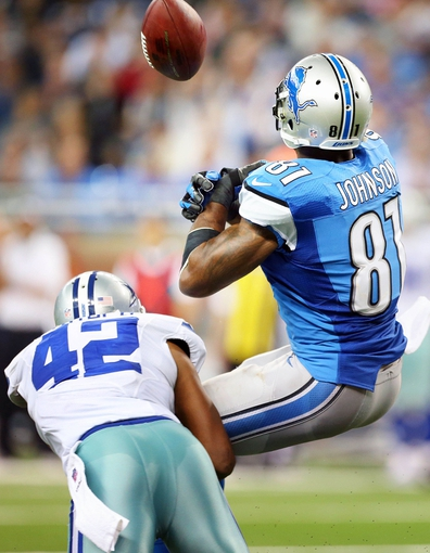 Oct 27, 2013; Detroit, MI, USA; Detroit Lions wide receiver Calvin Johnson (81) has ball knocked free by Dallas Cowboys free safety Barry Church (42) during 2nd half of a game at Ford Field. Lions won 31-30. Mandatory Credit: Mike Carter-USA TODAY Sports