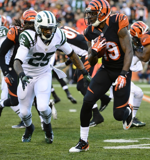 Oct 27, 2013; Cincinnati, OH, USA; Cincinnati Bengals wide receiver Brandon Tate (19) attempts to evade a tackle from New York Jets running back Alex Green (25) during the second half of the game at Paul Brown Stadium. Mandatory Credit: Marc Lebryk-USA TODAY Sports