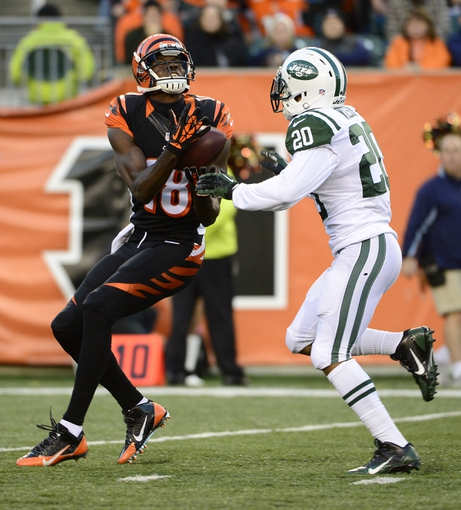 Oct 27, 2013; Cincinnati, OH, USA; Cincinnati Bengals wide receiver A.J. Green (18) catches a pass while being defended by New York Jets cornerback Kyle Wilson (20) during the second half of the game at Paul Brown Stadium. Mandatory Credit: Marc Lebryk-USA TODAY Sports