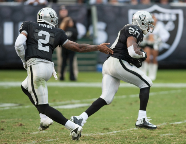 Oct 27, 2013; Oakland, CA, USA; Oakland Raiders quarterback Terrelle Pryor (2) hands the ball off to running back Darren McFadden (20) during the fourth quarter at O.co Coliseum. The Oakland Raiders defeated the Pittsburgh Steelers 21-18. Mandatory Credit: Ed Szczepanski-USA TODAY Sports