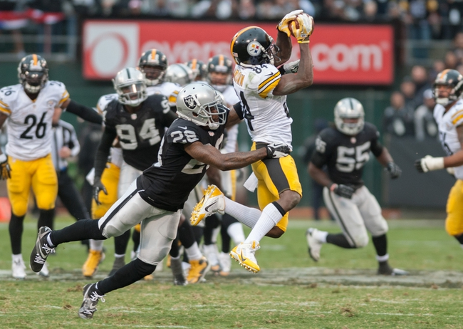 Oct 27, 2013; Oakland, CA, USA; Pittsburgh Steelers wide receiver Antonio Brown (84) catches a pass against Oakland Raiders cornerback Phillip Adams (28) during the fourth quarter at O.co Coliseum. The Oakland Raiders defeated the Pittsburgh Steelers 21-18. Mandatory Credit: Ed Szczepanski-USA TODAY Sports