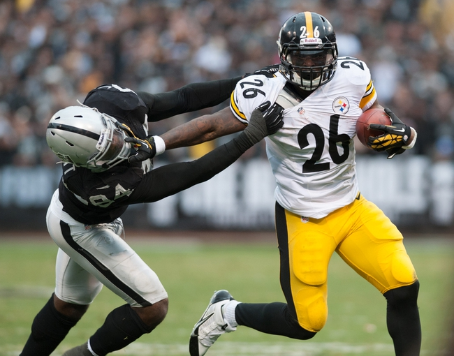Oct 27, 2013; Oakland, CA, USA; Pittsburgh Steelers running back Le'Veon Bell (26) straight arms Oakland Raiders outside linebacker Kevin Burnett (94) during the fourth quarter at O.co Coliseum. The Oakland Raiders defeated the Pittsburgh Steelers 21-18. Mandatory Credit: Ed Szczepanski-USA TODAY Sports