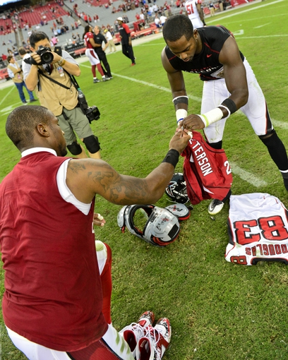 Oct 27, 2013; Phoenix, AZ, USA; Arizona Cardinals cornerback Patrick Peterson (21) and Atlanta Falcons wide receiver Harry Douglas (83) sign and exchange jerseys after the game at University of Phoenix Stadium.  The Cardinals beat the Falcons 27-13.  Mandatory Credit: Matt Kartozian-USA TODAY Sports