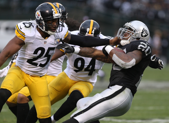Oct 27, 2013; Oakland, CA, USA; Oakland Raiders running back Darren McFadden (20) carries the ball against Pittsburgh Steelers free safety Ryan Clark (25) during the fourth quarter at O.co Coliseum. The Oakland Raiders defeated the Pittsburgh Steelers 21-18. Mandatory Credit: Kelley L Cox-USA TODAY Sports