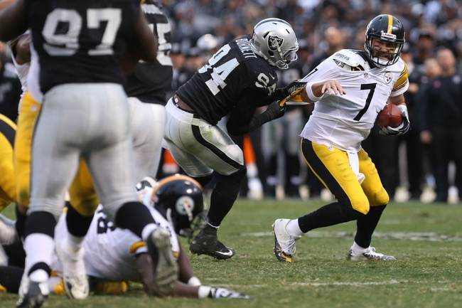 Oct 27, 2013; Oakland, CA, USA; Oakland Raiders outside linebacker Kevin Burnett (94) holds on to Pittsburgh Steelers quarterback Ben Roethlisberger (7) during the fourth quarter at O.co Coliseum. The Oakland Raiders defeated the Pittsburgh Steelers 21-18. Mandatory Credit: Kelley L Cox-USA TODAY Sports
