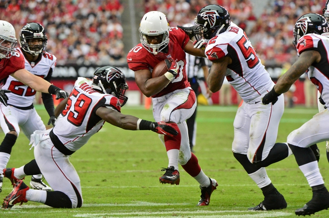 Oct 27, 2013; Phoenix, AZ, USA; Arizona Cardinals running back Stepfan Taylor (30) carries the ball as Atlanta Falcons middle linebacker Akeem Dent (52) and outside linebacker Joplo Bartu (59) defend during the second half at University of Phoenix Stadium. Mandatory Credit: Matt Kartozian-USA TODAY Sports
