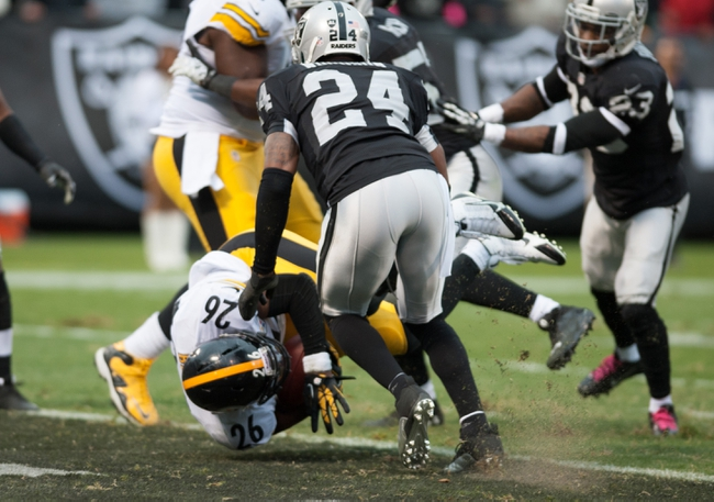 Oct 27, 2013; Oakland, CA, USA; Pittsburgh Steelers running back Le'Veon Bell (26) rushes for a touchdown against the Oakland Raiders during the fourth quarter at O.co Coliseum. The Oakland Raiders defeated the Pittsburgh Steelers 21-18. Mandatory Credit: Ed Szczepanski-USA TODAY Sports