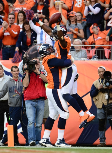 Oct 27, 2013; Denver, CO, USA; Denver Broncos wide receiver Demaryius Thomas (88) celebrates his touchdown with Denver Broncos guard Zane Beadles (68) in the fourth quarter against the Washington Redskins at Sports Authority Field at Mile High. Mandatory Credit: Ron Chenoy-USA TODAY Sports