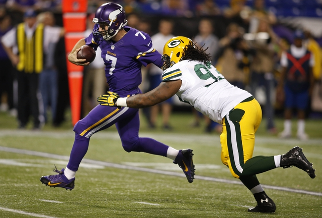 Oct 27, 2013; Minneapolis, MN, USA; Minnesota Vikings quarterback Christian Ponder (7) eludes the grasp of Green Bay Packers defensive end Josh Boyd (93) and rushes for a touchdown in the fourth quarter at Mall of America Field at H.H.H. Metrodome. The Packers win 44-31. Mandatory Credit: Bruce Kluckhohn-USA TODAY Sports