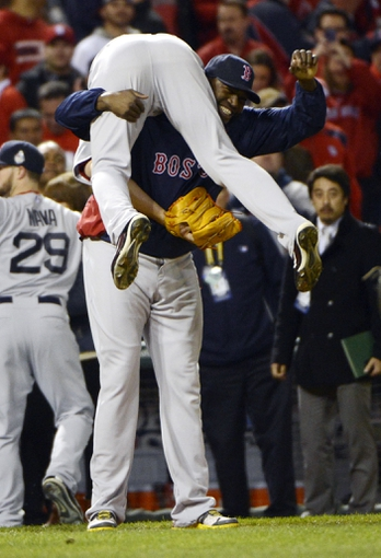 Oct 27, 2013; St. Louis, MO, USA; Boston Red Sox first baseman David Ortiz (facing forward) picks up relief pitcher Koji Uehara after defeating the St. Louis Cardinals 4-2 in game four of the MLB baseball World Series at Busch Stadium. Mandatory Credit: Eileen Blass-USA TODAY Sports
