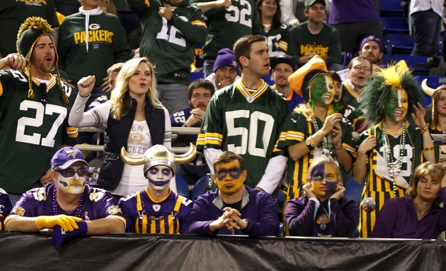 Oct 27, 2013; Minneapolis, MN, USA; A row of Green Bay Packers fans celebrate their team's success behind a row of Minnesota Vikings fans at Mall of America Field at H.H.H. Metrodome. The Packers win 44-31. Mandatory Credit: Bruce Kluckhohn-USA TODAY Sports