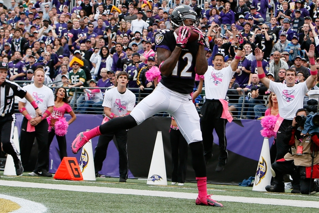 Oct 13, 2013; Baltimore, MD, USA; Baltimore Ravens wide receiver Jacoby Jones (12) catches a fourth quarter touchdown pass from quarterback Joe Flacco (not shown) against the Green Bay Packers at M&T Bank Stadium. Mandatory Credit: Mitch Stringer-USA TODAY Sports