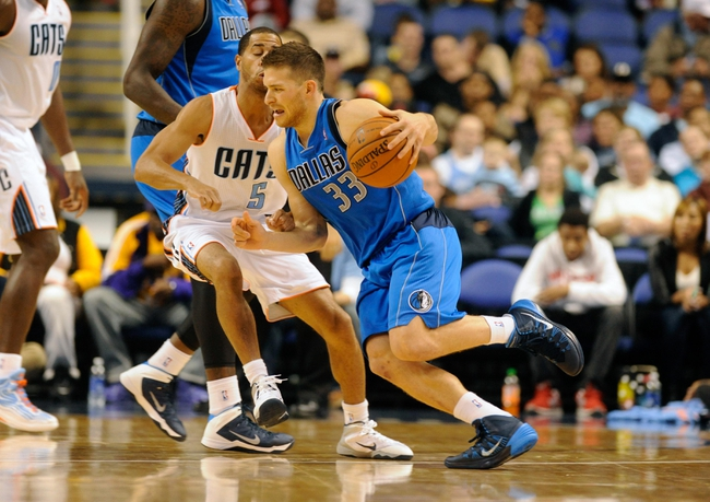 Oct 19, 2013; Greensboro, NC, USA; Dallas Mavericks guard Gal Mekel (33) drives past Charlotte Bobcats guard Jannero Pargo (5) during the game at the Greensboro Coliseum. Mavericks win 89-83. Mandatory Credit: Sam Sharpe-USA TODAY Sports