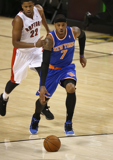 Oct 11, 2013; Toronto, Ontario, CAN; New York Knicks forward  Carmelo Anthony (7) drives to the basket as Toronto Raptors forward Rudy Gay (22) gives chase at Air Canada Centre. The Raptors beat the Knicks 100-91. Mandatory Credit: Tom Szczerbowski-USA TODAY Sports