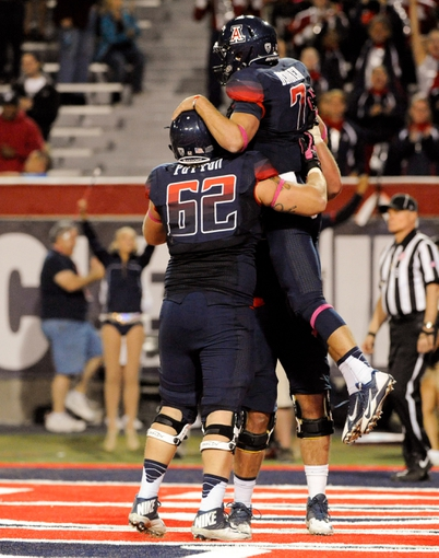 Oct 19, 2013; Tucson, AZ, USA; Arizona Wildcats offensive lineman Chris Putton (62) congratulates quarterback B.J. Denker (7) after a successful two point conversion during the fourth quarter against the Utah Utes at Arizona Stadium. Arizona beat Utah 35-44. Mandatory Credit: Casey Sapio-USA TODAY Sports