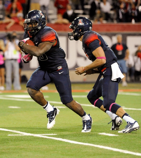 Oct 19, 2013; Tucson, AZ, USA; Arizona Wildcats running back KaDeem Carey (25) runs the ball after taking the hand off from quarterback B.J. Denker (7) during the third quarter against the Utah Utes at Arizona Stadium. Arizona beat Utah 35-44. Mandatory Credit: Casey Sapio-USA TODAY Sports