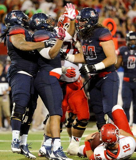 Oct 19, 2013; Tucson, AZ, USA; Arizona Wildcats defensive lineman Tevin Hood (98) defensive lineman Justin Washington (43) and defensive lineman Dan Pettinato (90) celebrate after sacking Utah Utes quarterback Adam Schulz (12) during the third quarter at Arizona Stadium. Arizona beat Utah 35-44. Mandatory Credit: Casey Sapio-USA TODAY Sports