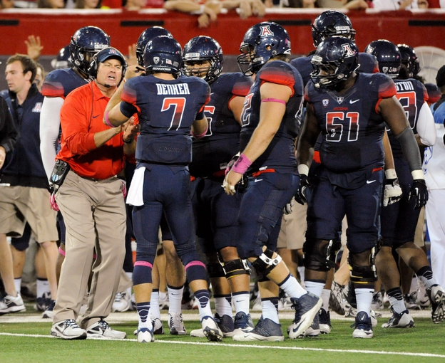 Oct 19, 2013; Tucson, AZ, USA; Arizona Wildcats head coach Rich Rodriguez talks strategy with quarterback B.J. Denker (7) in a team huddle during the fourth quarter against the Utah Utes at Arizona Stadium. Arizona beat Utah 35-44. Mandatory Credit: Casey Sapio-USA TODAY Sports