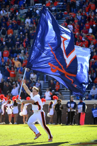 Oct 26, 2013; Charlottesville, VA, USA; Virginia Cavaliers cheerleader runs with a flag during the game. The Georgia Tech Yellow Jackets defeated the Cavaliers 35-25 at Scott Stadium. Mandatory Credit: Bob Donnan-USA TODAY Sports
