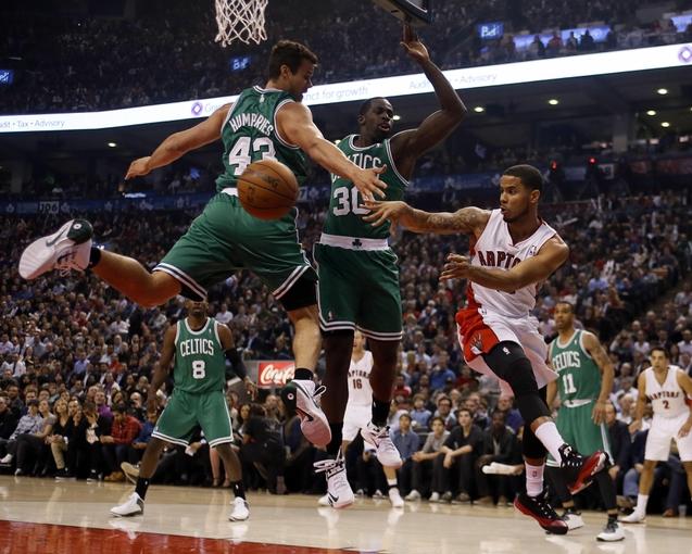 Oct 30, 2013; Toronto, Ontario, CAN; Toronto Raptors guard D.J. Augustin (14) passes the ball as Boston Celtics forward Kris Humphries (43) and forward Brandon Bass (30) defend during the first half at the Air Canada Centre. Mandatory Credit: John E. Sokolowski-USA TODAY Sports
