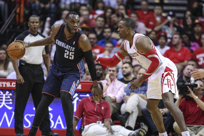 Oct 30, 2013; Houston, TX, USA; Charlotte Bobcats center Al Jefferson (25) controls the ball during the second quarter as Houston Rockets center Dwight Howard (12) defends at Toyota Center. Mandatory Credit: Troy Taormina-USA TODAY Sports