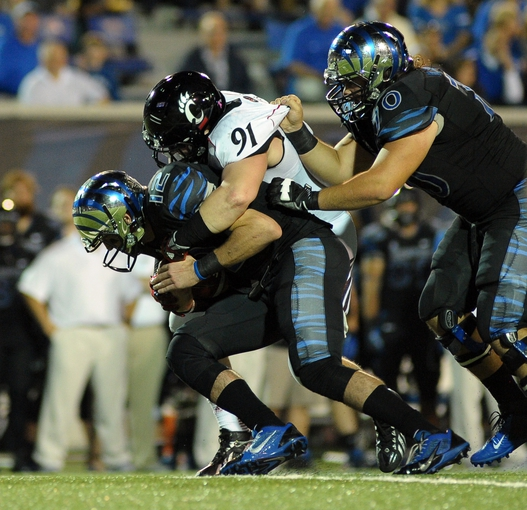 Oct 30, 2013; Memphis, TN, USA; Memphis Tigers quarterback Paxton Lynch (12) is sacked by Cincinnati Bearcats defensive tackle Adam Dempsey (91) during the second quarter at Liberty Bowl Memorial. Mandatory Credit: Justin Ford-USA TODAY Sports