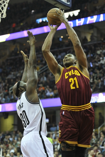 Oct 30, 2013; Cleveland, OH, USA; Cleveland Cavaliers center Andrew Bynum (21) shoots against Brooklyn Nets power forward Reggie Evans (30) in the first quarter at Quicken Loans Arena. Mandatory Credit: David Richard-USA TODAY Sports