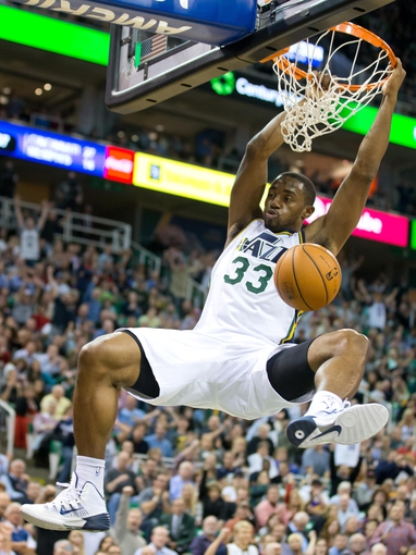 Oct 30, 2013; Salt Lake City, UT, USA; Utah Jazz small forward Mike Harris (33) hangs from the rim after dunking during the second half against the Oklahoma City Thunder at EnergySolutions Arena. Oklahoma City won 101-98. Mandatory Credit: Russ Isabella-USA TODAY Sports