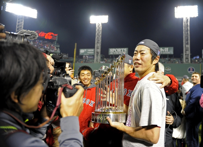 Oct 30, 2013; Boston, MA, USA; Boston Red Sox relief pitcher Koji Uehara celebrates on the field with the World Series championship trophy after game six of the MLB baseball World Series against the St. Louis Cardinals at Fenway Park. The Red Sox won 6-1 to win the series four games to two. Mandatory Credit: Bob DeChiara-USA TODAY Sports
