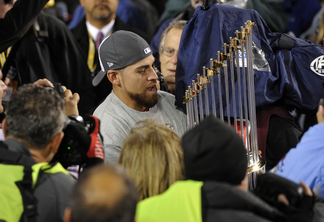 Oct 30, 2013; Boston, MA, USA; Boston Red Sox center fielder Jacoby Ellsbury carries the World Series championship trophy after game six of the MLB baseball World Series against the St. Louis Cardinals at Fenway Park. The Red Sox won 6-1 to win the series four games to two. Mandatory Credit: Robert Deutsch-USA TODAY Sports