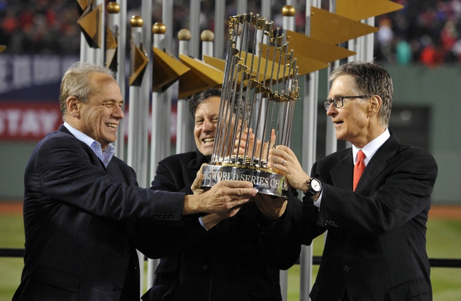 Oct 30, 2013; Boston, MA, USA; Boston Red Sox owners including John Henry (right) and Larry Lucchino (left) and Tom Werner (middle) hold the World Series championship trophy together after game six of the MLB baseball World Series against the St. Louis Cardinals at Fenway Park. The Red Sox won 6-1 to win the series four games to two. Mandatory Credit: Robert Deutsch-USA TODAY Sports