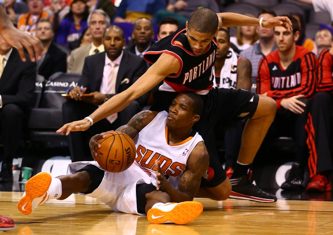 Oct 30, 2013; Phoenix, AZ, USA; Phoenix Suns guard Eric Bledsoe (bottom) is fouled by Portland Trail Blazers forward Nicolas Batum (88) in the fourth quarter at US Airways Center. The Suns defeated the Blazers 104-91. Mandatory Credit: Mark J. Rebilas-USA TODAY Sports