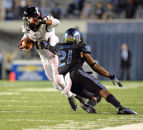 Oct 30, 2013; Memphis, TN, USA; Cincinnati Bearcats wide receiver Shaq Washington (19) is brought down by Memphis Tigers defensive back Bobby McCain (21) during the second half at Liberty Bowl Memorial. Cincinnati Bearcats defeated the Memphis Tigers 34 to 21 Mandatory Credit: Justin Ford-USA TODAY Sports
